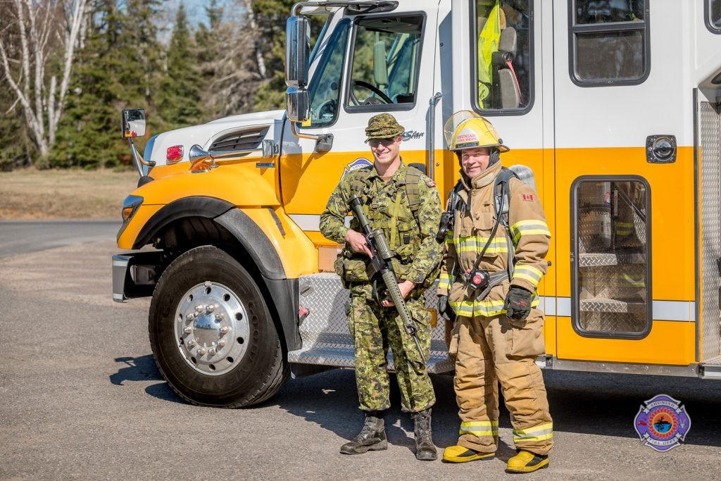 Firefighter and soldier in front of fire truck