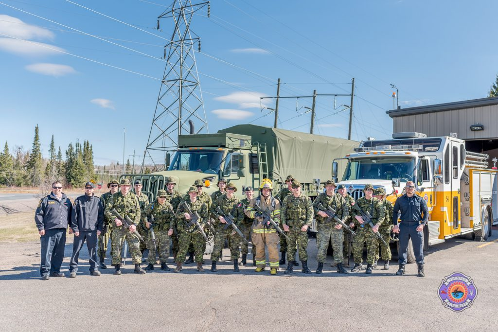 firefighters and soldiers pose together